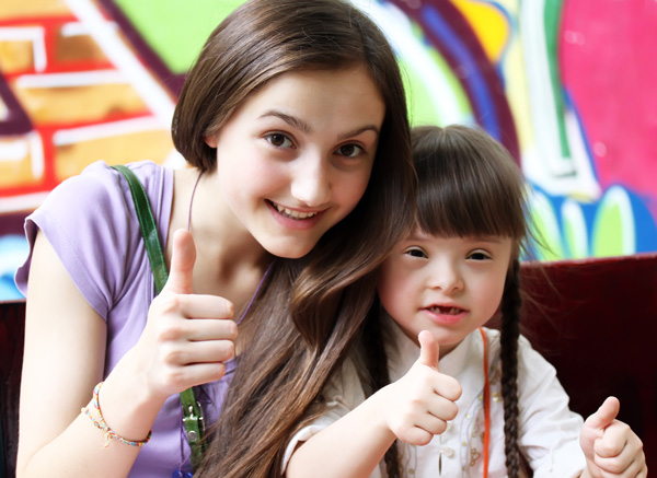 Two girls lifting their thumbs, one girl with disability